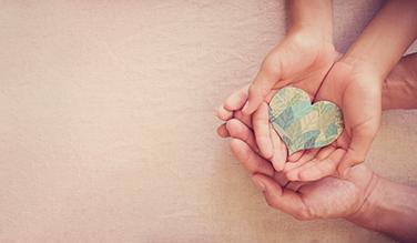 photo d'une main avec un coeur en papier